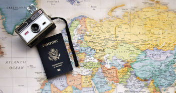 Passport and camera on a map of the world