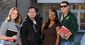 Group of diverse students standing in front of a suburban high school