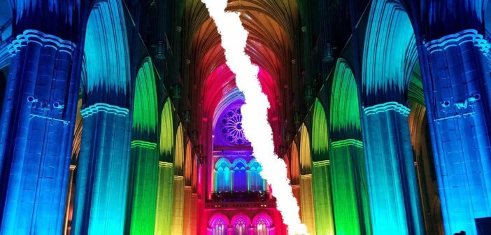 Ripped-in-half photo of the interior of a church lit in rainbow hues