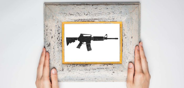 Hands holding a framed image of an assault rifle