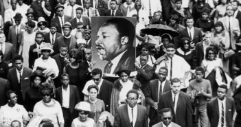 A large crowd of mourners follow the casket of Dr Martin Luther King Jr through the streets of Atlanta, Georgia. Two men carry a large sign with King's face. CREDIT: Hulton Archive / Getty Images / Universal Images Group