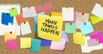 Cork board full of thumbtacked notes including a big one that says MAKE THINGS HAPPEN!