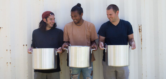 Three smiling volunteers holding large, heavy cooking pots