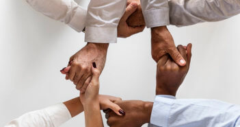 Diverse group of people clasping hands together