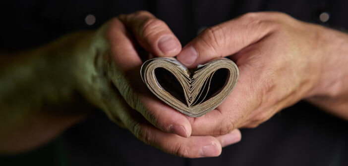 Person's hands holding paper currency folded into the shape of a heart