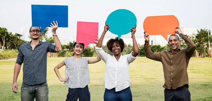 Four millennials holding up cardboard speech bubbles