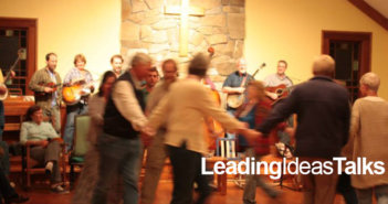 People whirling in a circle to live bluegrass music at a square dance at Wild Goose Christian Community
