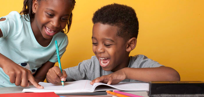 Smiling kids writing in a notebook