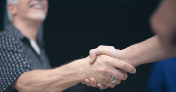 Person warmly shaking hands with another
