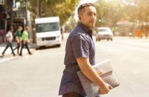 Young pastor carrying a laptop bag while crossing a city street