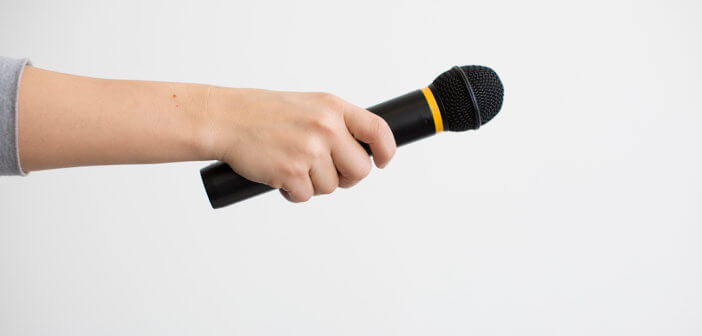 Hand passing a microphone to someone for an introduction