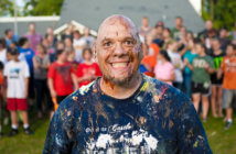 Grinning paint-spattered church youth leader standing in front of a group of youth