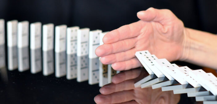 Hand trying to stop dominoes from falling