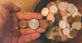 Close up of a hand dropping coins into a collection plate