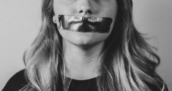 Black and white photo of a woman silenced by tape covering her mouth