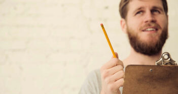 Person in thought while holding a clipboard and pencil