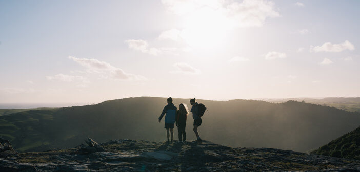 Hikers atop a large hill
