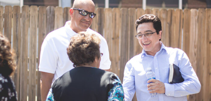 Pastor and church member outside speaking with a community member