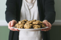 Person offering a plate of delicious cookies