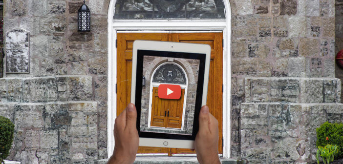 Person holding up a tablet with an image of a church door in front of said church door