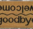 Floor mat that reads goodbye on one side and welcome on the other