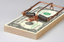Mouse trap on a stack of cash bills