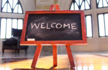 Easel with WELCOME written in chalk in a church sanctuary