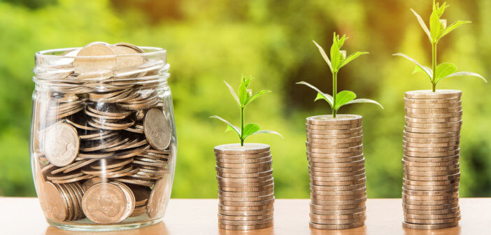 Jar of coins beside growing stacks of coins with seedlings sprouting from the top