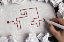 Person working successfully through a maze on pen and paper