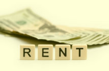R E N T spelled out on tiles in front of a stack of cash