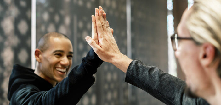 Smiling people giving each other a high five