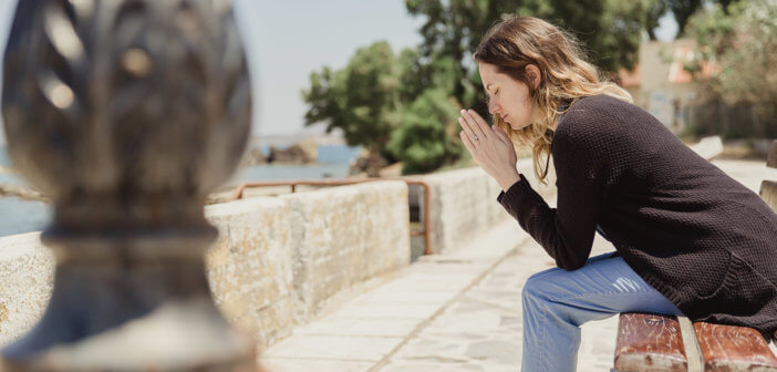 Person saying a prayer sitting on a bench
