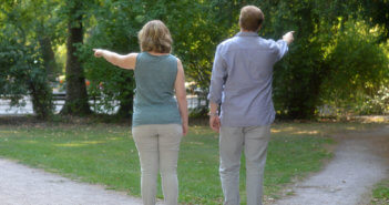 Two people pointing in different directions while standing on the crossroads of a path