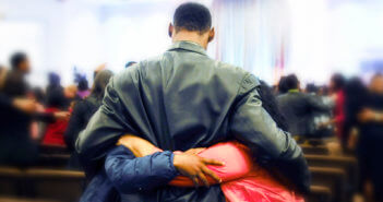 A person receiving hugs in a church sanctuary