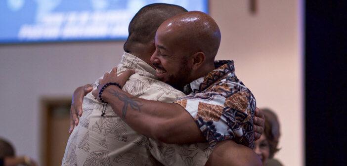 Smiling church members sharing a hug