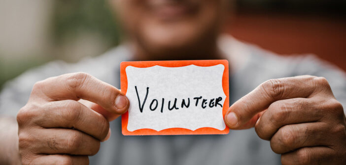 Person holding a VOLUNTEER name tag