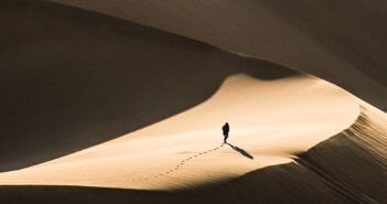 Person walking alone in a vast desert