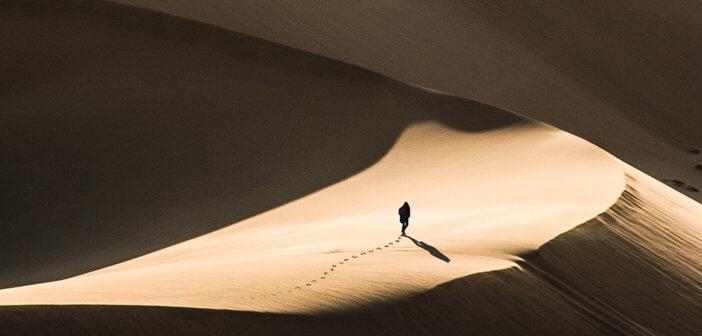 Person walking alone in a vast desert