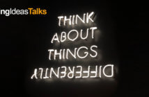 Neon sign reading THINK ABOUT THINGS DIFFERENTLY with differently spelled upside down