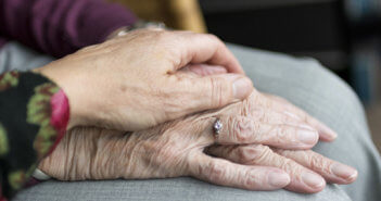 Person holding the hand of an older adult