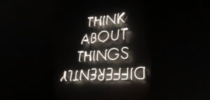 Neon sign reading THINK ABOUT THINGS DIFFERENTLY -- and differently is upside down