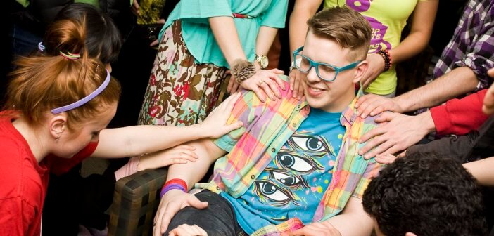 Teen sitting in chair while friends place their hands on his shoulders and arms.