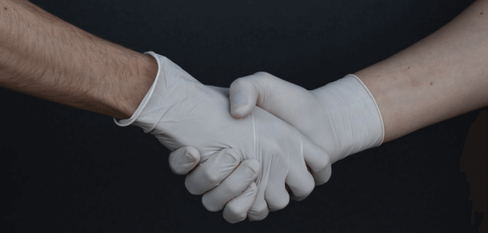 Shaking hands while wearing medical gloves