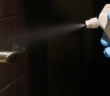 Spraying disinfectant on a doorknob