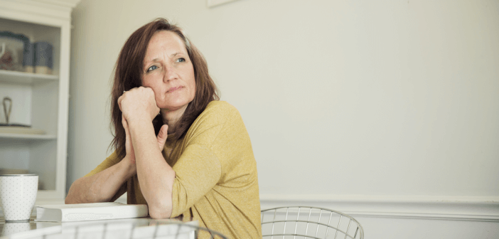 Middle-aged person sitting pensively at a table