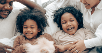Children and parents laughing together in bed