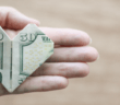 $50 bill folded into an origami heart in the open palm of a person's hand