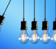 A lightbulb hanging on a cord crashing into four other lightbulbs on cords