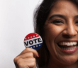Smiling person holding a VOTE button