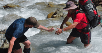 Backpacker lending a hand to help another cross a stream